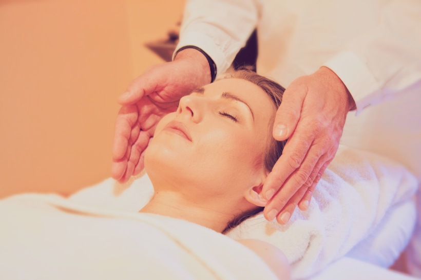 Reiki Practitioner Holding Their Hands on Either Side of the Recipient's Head While They Relax on a Massage Table
