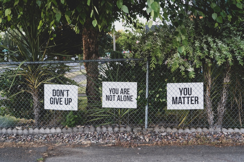"Three white signs behind a metal fence write, ""Don't Give Up,"" ""You Are Not Alone,"" and ""You Matter."" There are lush, green trees behind the signs and a road in front of the fence."