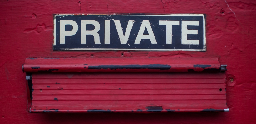 "A red-painted door with a ""PRIVATE"" sign in black with white lettering, which signifies the importance of data privacy through decentralized cloud storage and social media in a world of centralized surveillance, data misuse, and breaches."